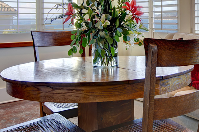 Cherry wood dining room table with floral arrangement